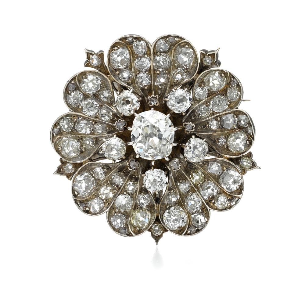 古典枕形切割钻石胸针,此款钻石花型胸针使用了两种不同的钻石切割方式枕形切割和玫瑰形切割。中央主石为2.1克拉古典枕形切割钻石。枕形切割钻石也被称为老矿工切割,盛行于18世纪到19世纪中期。这种切割方式早于老式的欧式切割钻石,需要手工切割。其特点是形状为方形,但是四角呈圆形,如同枕头一般
