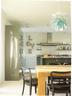 """厨房中的吊灯伸展出层层叠叠的淡绿色"""" 叶片"""",同窗外近在咫尺的绿茵热络地联系起来。定制厨房由这栋房子的建筑师完成,不锈钢的岛台、宽大的木餐桌,都是主人用餐的好选择,岛台下的黑色圆凳来自Diesel的家居系列。"""