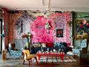 """""""我运用流畅的色彩和线条把家装饰得更突出、有趣。""""比如那面彩绘的墙,特别加了些紫红色和黄色,效果格外出跳。客厅的左侧,是扶手椅和复古情调浓郁的布艺沙发。茶几上摆放着精致有型的陶瓷摆件、烟灰缸、和零散的各式茶具。墙壁上悬挂的花朵壁画和装饰物,体现着后现代主义的风格。"""