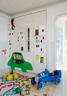 """游乐室的壁柜门充满童趣,楼宇、汽车、云朵的形象,让这里变成一座热闹的""""卡通城市""""。儿童游乐室中,Silvia设计了一整面墙的壁柜,用来盛放孩子们的玩具和书籍。Eco City地毯由毯言织造出品,蓝色的英国Baghera品牌复古童车来自Lane Crawford连卡佛,车上的木头人偶是Alexander Girard为Vitra设计的,来自10 Corso Como,南瓜装饰靠枕是艺术家草间弥生的作品。"""