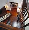 布满厅堂的桃花心木,以它浓郁的棕红带来一种阳刚的温暖,柔和的纹理与色泽在光线的映衬下 尤其显出沉稳的气质。拥有双层层高的门厅,开放式的楼梯连接着二层的客卧以及房子的东翼。那里是家中两个孩子的地盘。在主楼梯下方的木饰面墙壁上,藏着一扇暗门,可以通向地下室和佣人区。从楼上俯视被桃花心木包裹的门厅,条案下的古董日本大罐来自Manoukian Noseda。