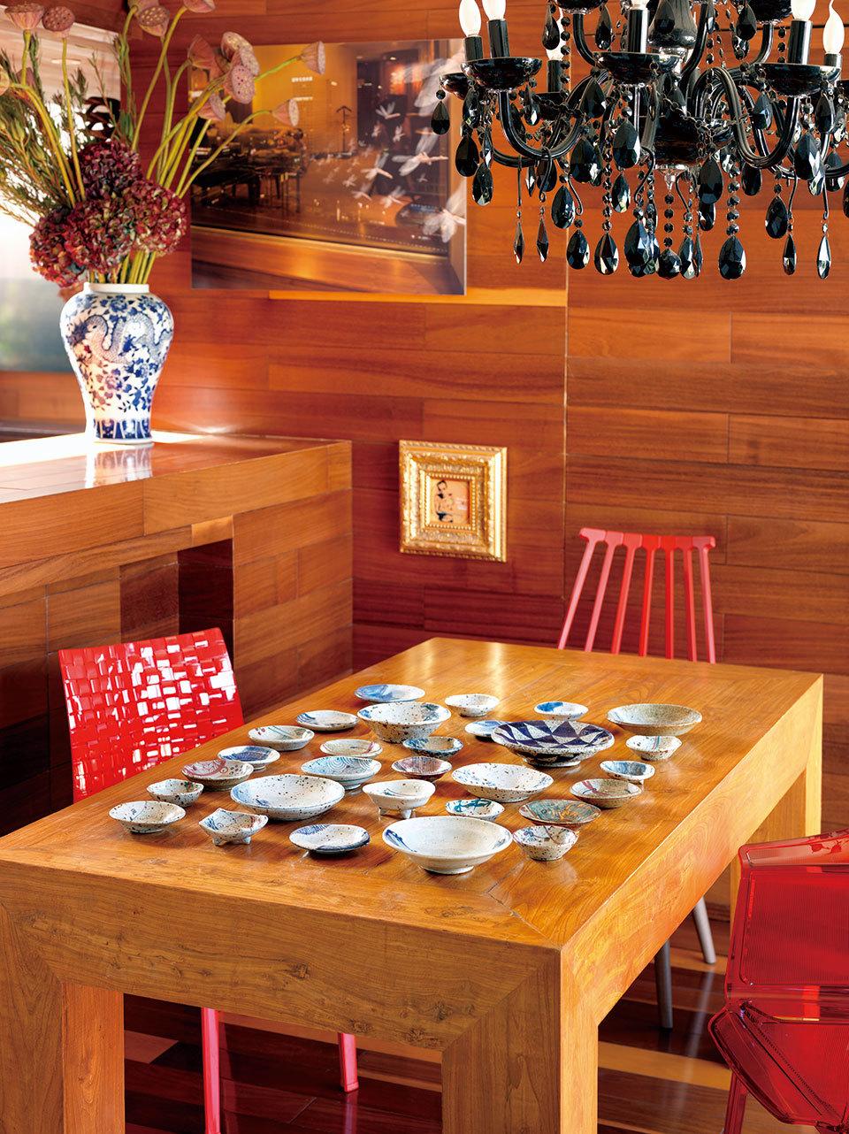 餐桌上摆满朴拙小碗碟,黑色吊灯却透着点华丽感,颇有设计感的红椅子来自Kartell。