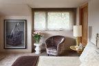 主卧,墙上的摄影作品出自艺术家William Wegman之手。放置鲜花的白色小凳来自Serge Castella Interiors,丝绒面扶手椅同样由Serge Castella Interiors设计。设计师Oppenheim设计的小桌上,摆放着一盏上世纪60年代的金色法国台灯。