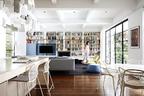 整面墙的大书架宣告了主人那些藏书在这个家中的绝对地位,色彩绚烂的书脊与户外泳池边上的艺术品产生着共鸣。客厅中,琳琅满目的书籍成了最漂亮的墙面装饰,由Lucy Marczyk设计的书柜专门配备了方便取阅图书的梯子。L形的Charles沙发、两张黄色安乐椅Lazy 05、白色Frank小茶几以及蓝色的Fat沙发脚凳均来自B&BItalia,白色的Flos落地灯Ray立在一旁。近处左侧是厨房岛台,来自 IngoMaurer的Zettel'z 5吊灯带来浓厚的生活气息。两只Accademia的白色Vela吧凳以其编织的镂空图案呼应着右侧圆桌旁的Kartell Masters餐椅,纯白的Glossy餐桌同样出自Kartell。