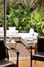 年轻家庭庭院的起居室外有一个绿意沃若的露天平台,现代风格的沙发也是另一份设计宣言。