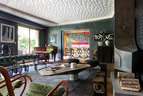 起居室的墙面重新覆以暗色的织纹树脂,来自Signature Murale;地板材料为云杉。透过起居室的移门可以看到餐厅。