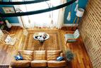 从二楼走廊俯瞰整个客厅,落地窗为这个空间带来明亮的光线和完美的景色。