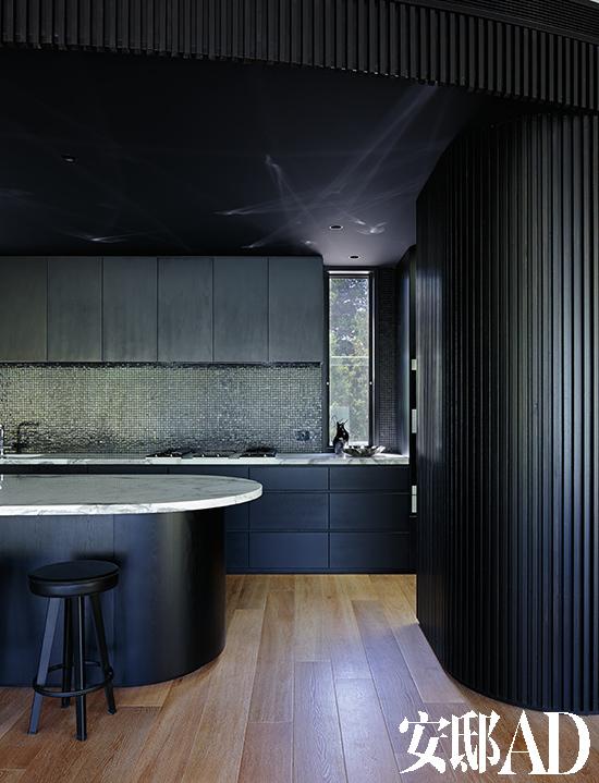 椭圆形的岛台和弧形的墙面为有些冷峻的深色厨房带来变化与韵律.