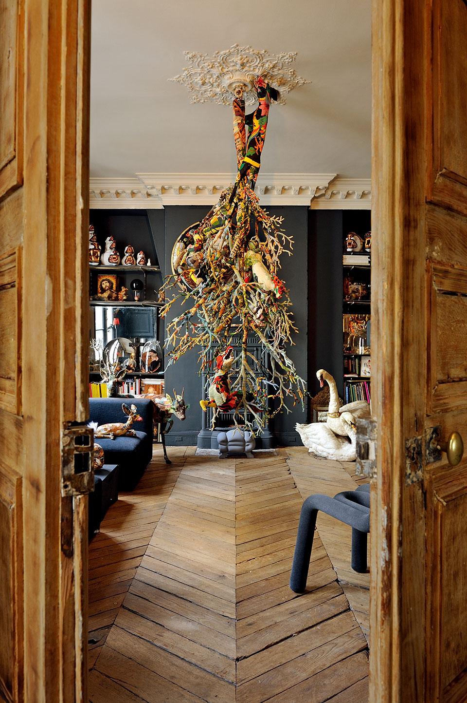 """壁炉前,一棵针织面料拼接制作的圣诞树从天花板上悬垂下来。墙壁、椅子和沙发都是浓重的铁灰色,更衬托出彩色""""圣诞树""""与众多拼布动物玩偶的绚丽多姿。"""