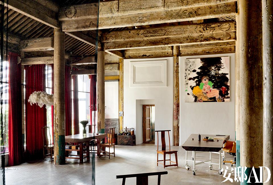 """楠木柱子支撑着颜色几乎完全剥落尽了的屋梁,色 彩该是有一部分掉进了白墙上冰逸的画中。大厅疏朗开阔,足以起舞。灯光、隔墙等的改造都没有减去原本、结构的风韵。墙上悬挂的是冰逸的油画作品系列"""" 皮肤""""之《女王》( Queen)。"""