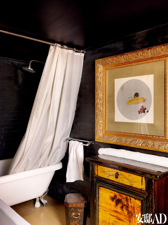 加建的卫生间墙面、屋顶全部刷成黑色,旧式家具、西式画框和现代卫浴以一种合理的关系共同存在着。
