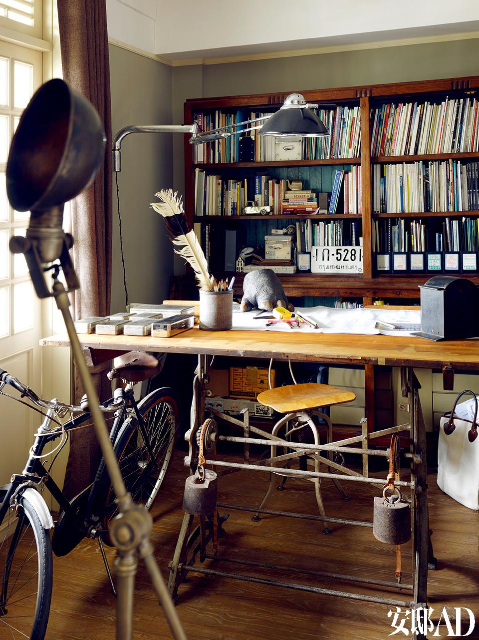 """二战时期的医院手术灯与被割下来的河马脚就这样活生生地围绕书桌旁,这都是在泰国挖掘到的重口味收藏。叶裕清的工作桌之一,桌子为二战时期的产品,即使现在人多在电脑上做设计了,但他依旧钟爱这""""古味""""!桌上为牙医专用的老灯,桌上的""""怪物""""是一只河马的脚!"""