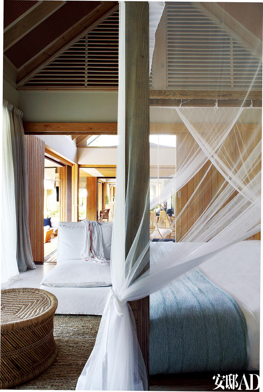 卧室中央的四柱床由岛上当地的木匠和手工艺人用硬木制成,非常坚实耐用,躺在床上就可以看到海景,白色幔帐又为居室平添一抹朦胧。卧室内简约的扶手椅采用了白色亚麻布座套,地上摆放的则是用海草编织的垫子和来自印度的芦苇凳。