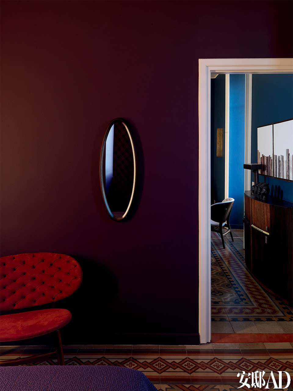 卧室与客厅相连的紫色墙面上,一面椭圆形古董镜,好像为整个空间添了一只神秘的眼睛。卧室里的墙面被漆成紫色,木框古董镜与来自Baxter的红色当代扶手椅和谐相处,呼应着地砖的红色,这里的视线能够望见客厅。