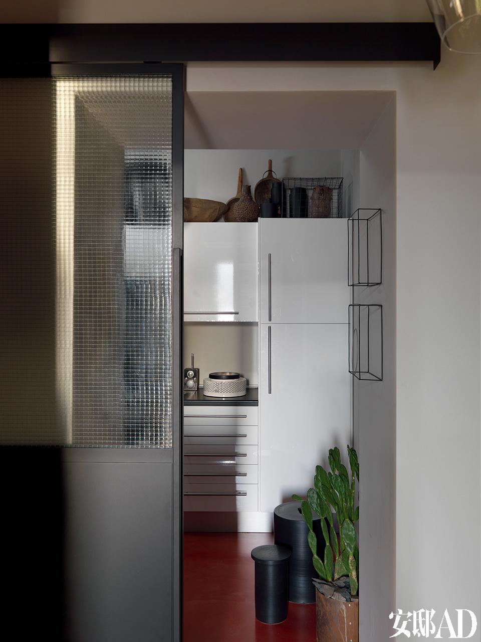 工业风格的滑动门可以通往家中的厨房,厨房的架子上陈列着一系列民族和现代风格的物件,为原本稍显平淡的厨房增添了质感和氛围。厨房墙壁上的金属丝雕塑是由Antonino Sciortino创作的。
