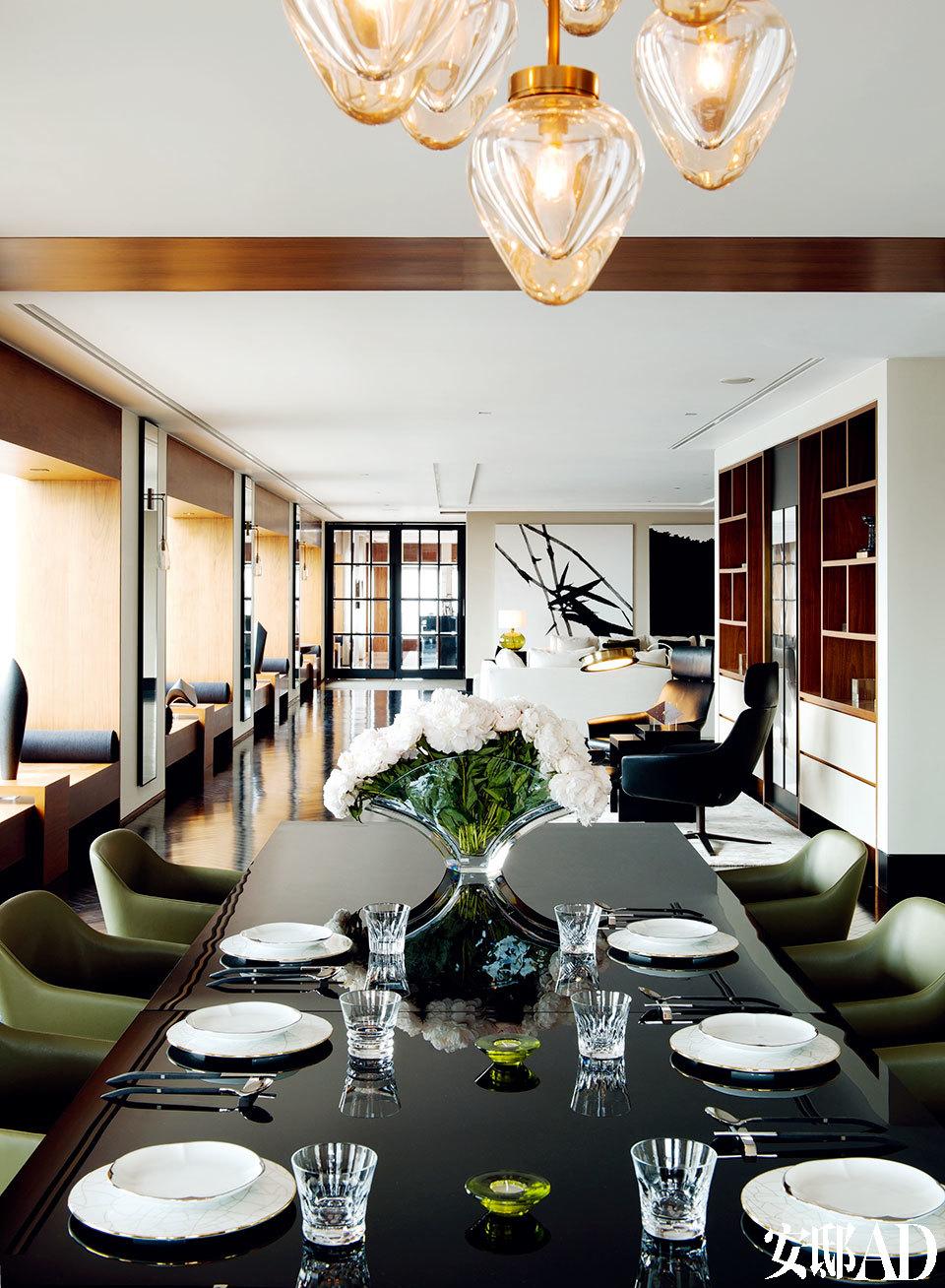 木盒子般的窗体整齐划一地向远 处延伸,窗与窗之间的镜面壁灯就像音乐中的休止符,给狭长的空间带来视觉上的喘息。从餐桌看向客厅以及法式对开玻璃门后的书房区,近处餐桌上的银杏叶花瓶来自Baccarat,靠窗一侧墙面上的Holly Hunt壁灯由Alison Berger设计,每座窗台上都摆放着一尊由埃及艺术家Armen Agop创作的黑色花岗岩雕塑。
