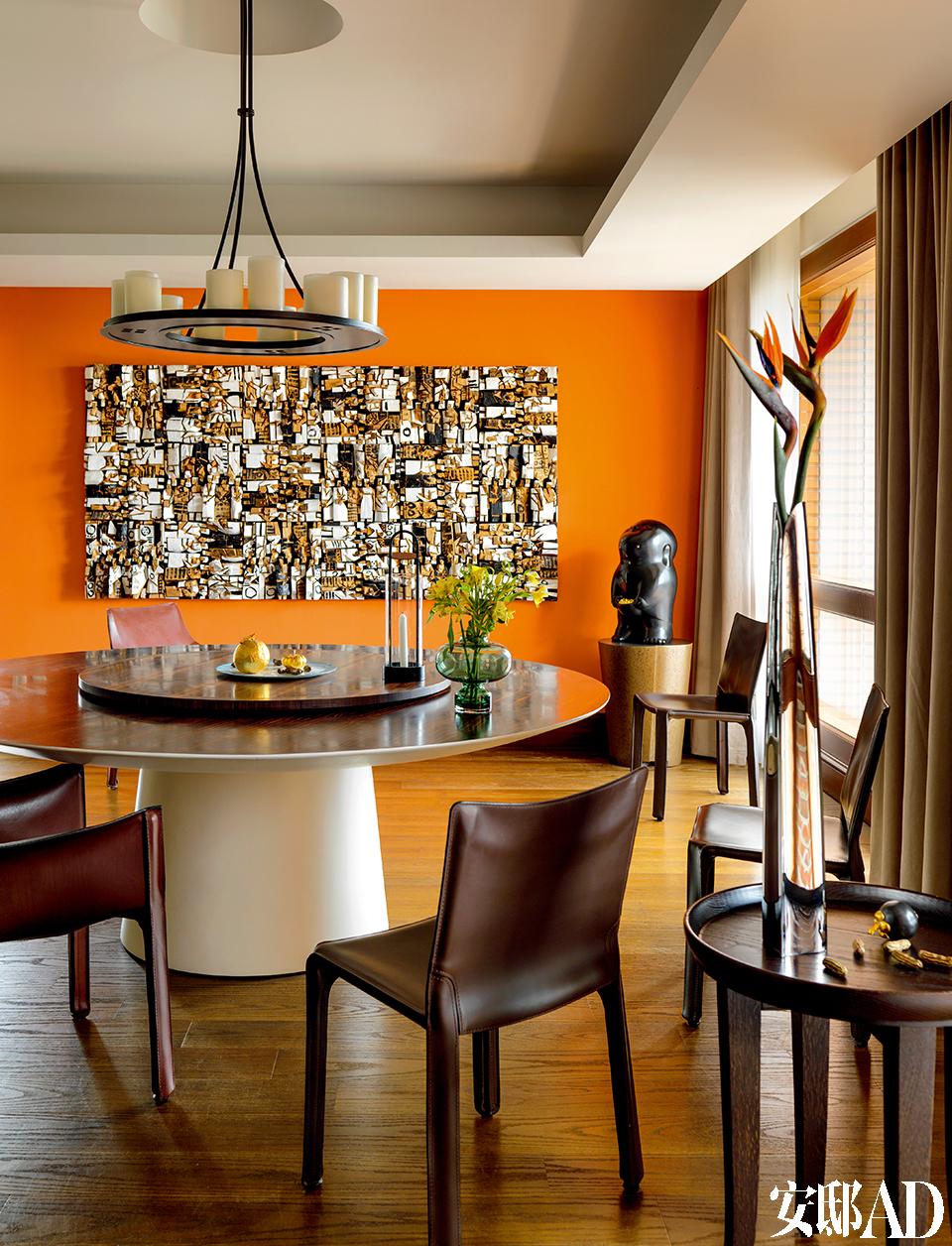 """这个圆形的中式餐桌是这个家的""""核心"""",主人补起餐桌对面原本为落地玻璃的这面墙,刷成具有西班牙风情的橘色,再挂上朱铭代表作品《人间系列》,都是为了一个""""暖""""字。"""