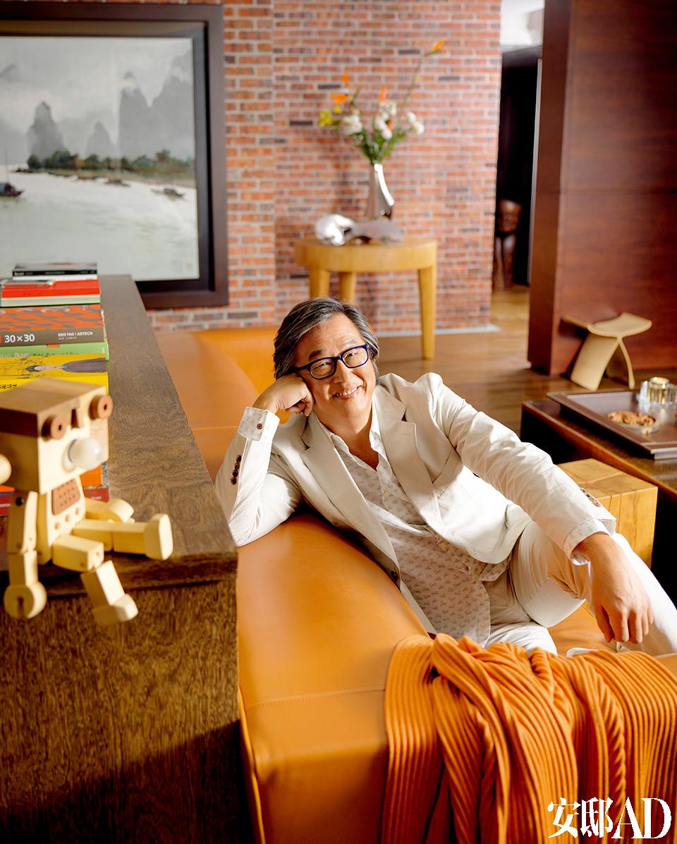 """主人: 王伟忠,1957年10月26日出生于台湾嘉义,祖籍北京,是台湾地区最著名的电视节目制作人和经纪人之一。他毕业于中国文化大学新闻系,现任金星娱乐总经理。他担任制作人的《康熙来了》是迄今为止在两岸三地影响力最大、最走红的综艺节目 之一。此外,他制作过的代表性节目还包括《国光帮帮忙》《我猜我猜我猜猜猜》和《超级星光大道》等。此外,他还是台湾眷村文化的推广人。2008年,他导演的话剧《宝岛一村》公映并获得第一届北京丹尼国际舞台表演艺术奖最佳编剧奖。同时,他还拥有眷村菜手信品牌""""福忠"""",著有《伟忠姐姐的眷村菜》等书,还拍摄了纪录片《想我们的眷村妈妈》及《伟忠妈妈的眷村》等。 王伟忠现在是这个家中待在家时间最长的成员。他背后那面红砖墙是老家嘉义的眷村拆迁时,他赶回去运回来的老砖,他要自己不论身在哪里,都不忘那段眷村岁月。"""