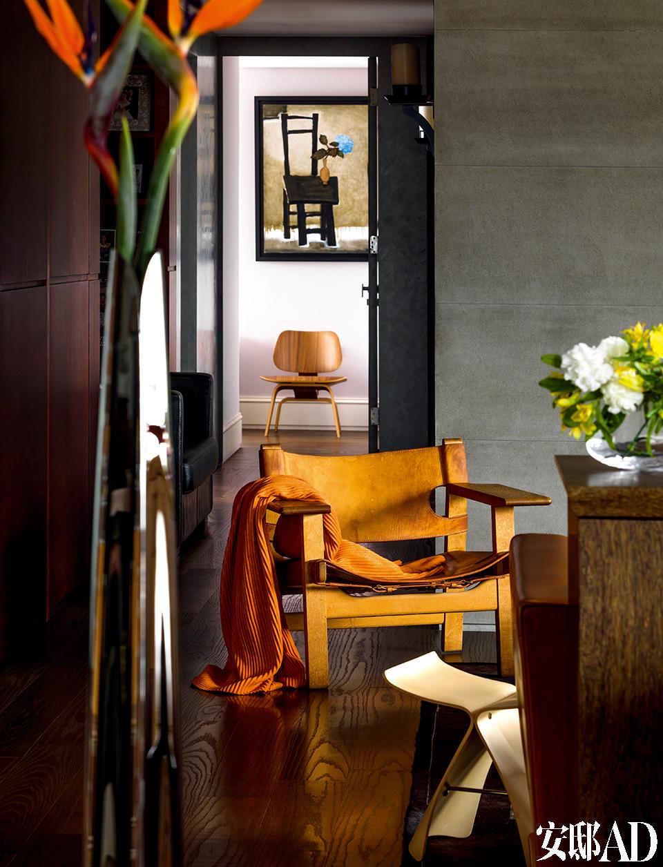 """从客厅经走廊可以看到女儿房 间的墙壁,王伟忠专门为女儿挑选了董小蕙的""""黑椅子""""油画作品,因为他觉得它既优雅又有家的感觉。来自Børge Mogensen设计的""""西班牙椅""""(丹麦仓库提供),其椅子上的橘色毛毯来自品牌Design House Stockholm(北欧橱窗提供)。"""