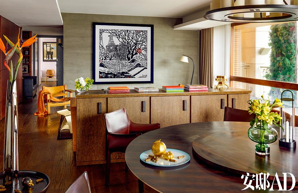 """客厅与餐厅开放相连,全南向大落地窗带来极好的光线,所以他用了深木色和皮质等稳重元素来平衡。墙上挂着有关白塔的艺术品,那是王伟忠心心念念的故乡——北京。餐厅与客厅是连通一体的。Armani Casa的大圆餐桌 上摆着Living Georg Jensen的""""Tea with Georg""""晕蓝瓷盘组 和""""Alfredo""""手工花瓶、Design House Stockholm Lotus的 """"守护灯塔""""摆件;左侧茶几上则摆着Living Georg Jensen的 """"Indulgence系列花瓶"""",皆由北欧橱窗提供。Promemoria的木质餐柜上的""""泡泡糖先生""""灯具为台湾设计师银济春设计,Anadou木作出品(丹麦仓库提供)。餐椅为Cassina出品,餐桌吊灯为Holly Hunt出品。"""