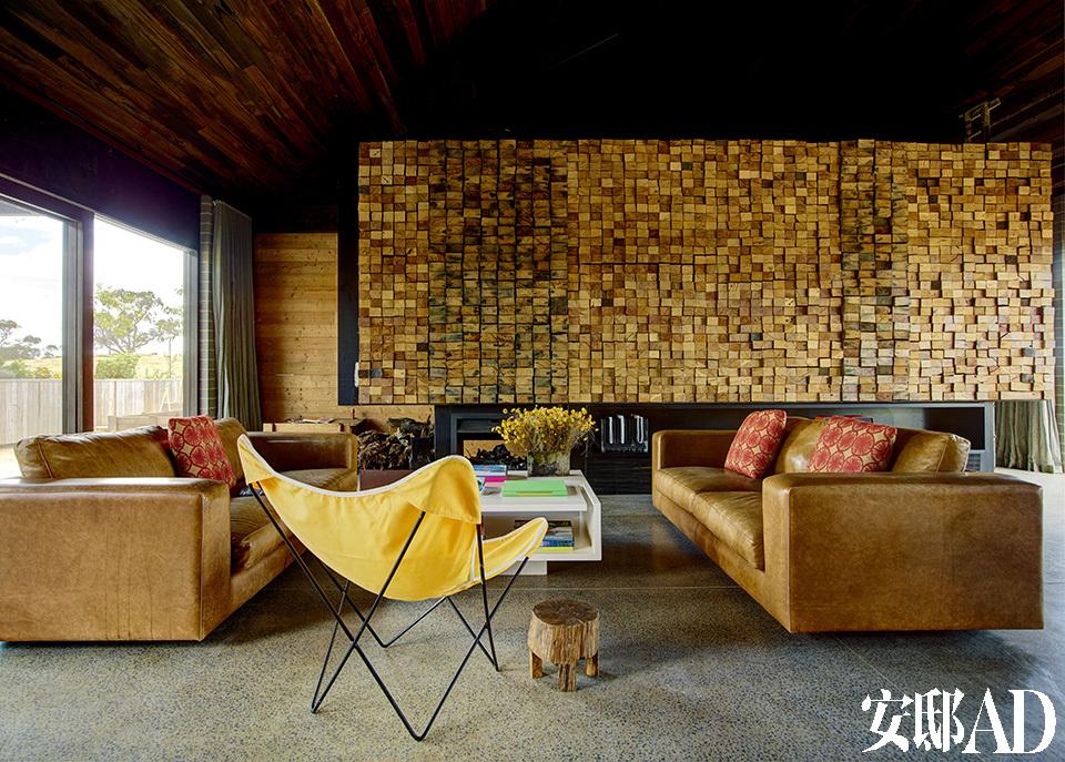 1680块用来铺设木地板基底的废旧木料,主人当初只因为好看,很便宜地收了回来,最后却出人意料地成就了这面美丽自然的壁炉墙。房屋中央是起居室和厨房,四周是大大的落地窗。地板选用了抛光混凝土材质,天花板则沿用了黑基木。壁炉墙由1680块木料构成,沙发和咖啡中由Jerry Wolveridge自己设计,黄色座椅来自Butterfly Chair,矮凳购自东京。
