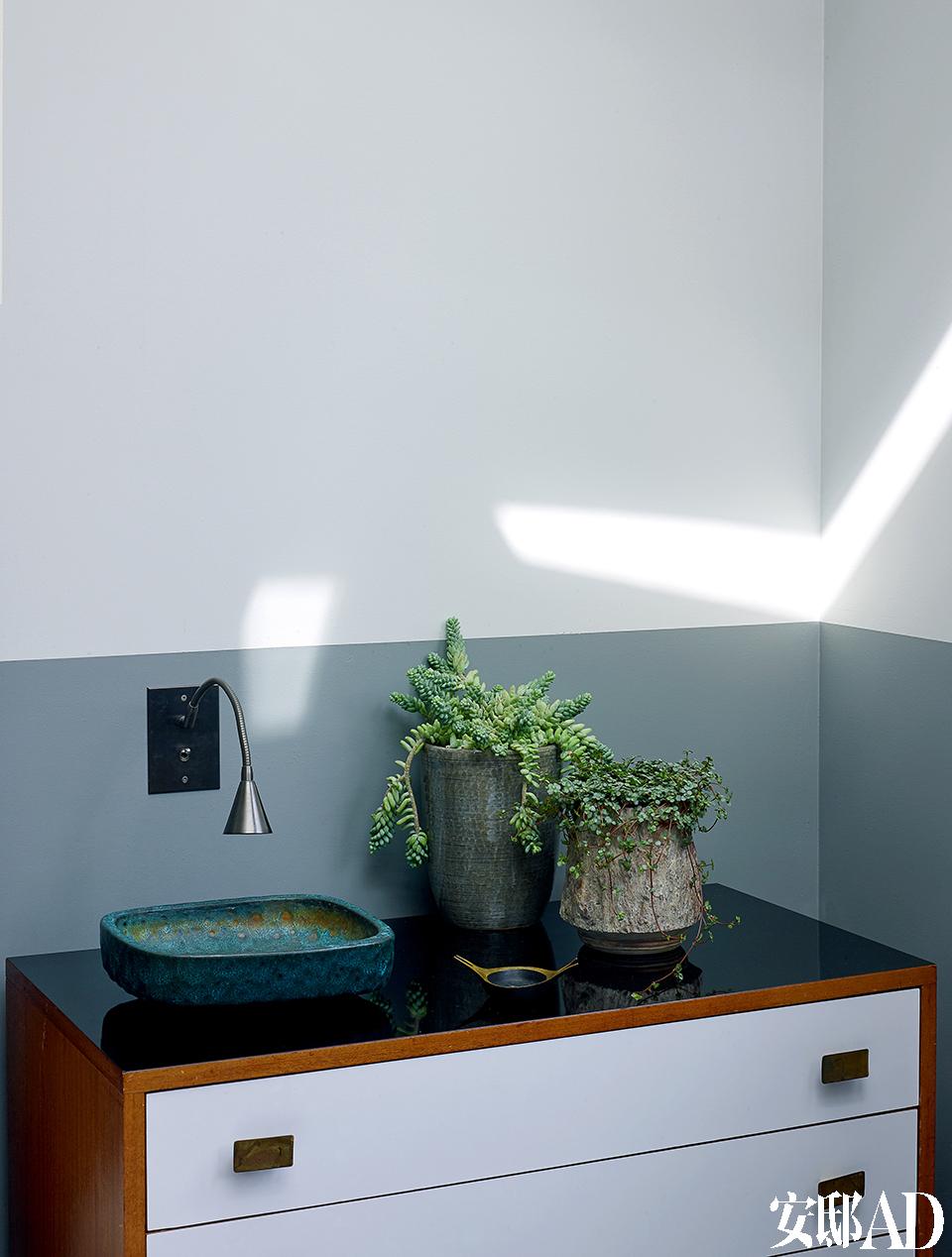 床头抽屉柜上的铜绿储物小缸是以现代风格著称的奥地利设计师、画家Carl Aubock的作品。墙上的小壁灯由业界公认的全球最 美铜开关板制造商、法国品牌Meljac出品。