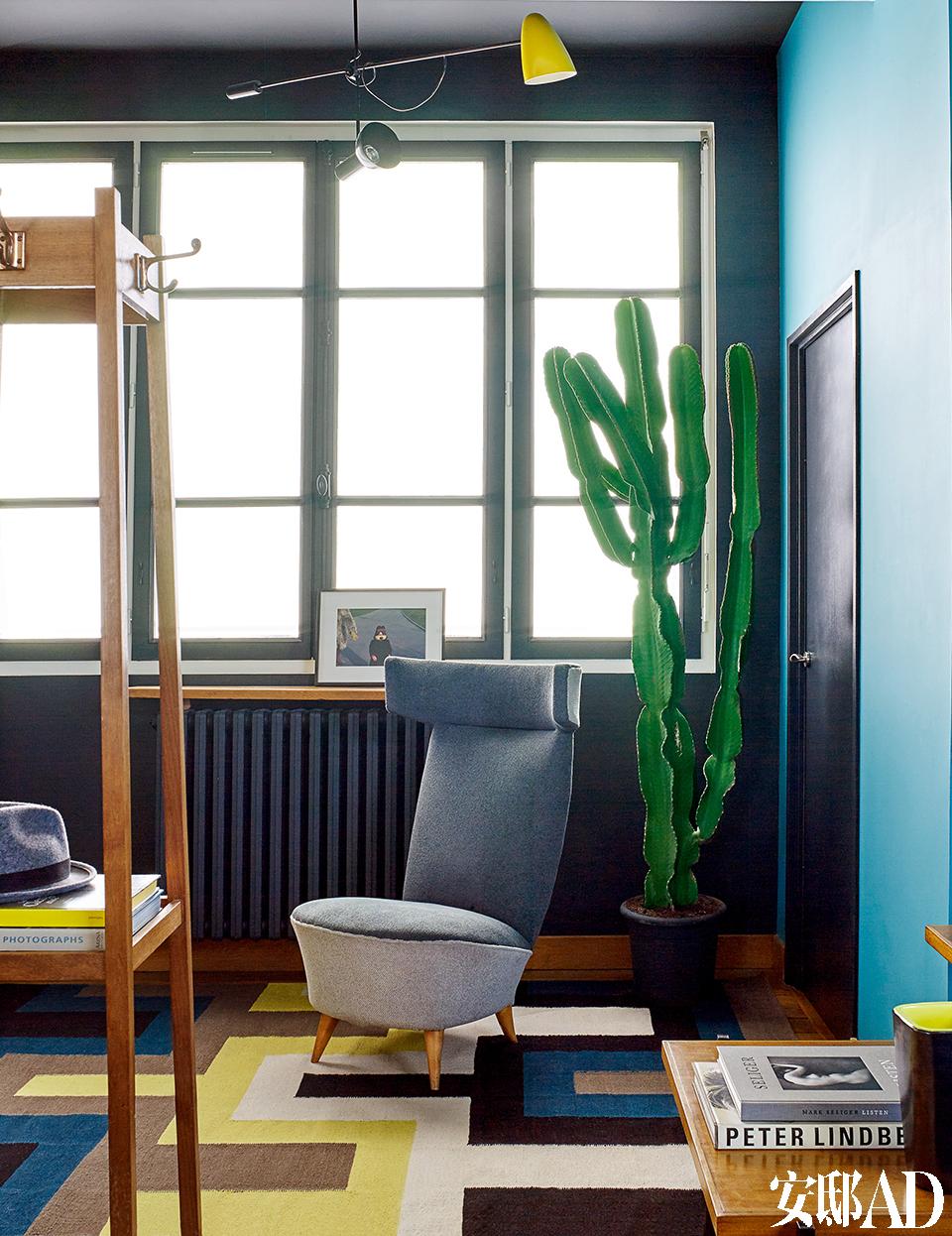 一进门一块几何图案的地毯, 已经让家里的几个主要颜色一一和客人打过招呼,好像明艳的序曲, 迷人又不失礼貌。进门处,20世纪50年代出品的意大利古董矮脚凳摆在玄关正中,旁边竖立着新艺术运动风格的多功能衣架。吊灯来自Jacques Biny,地毯由Lindell & Co出品。