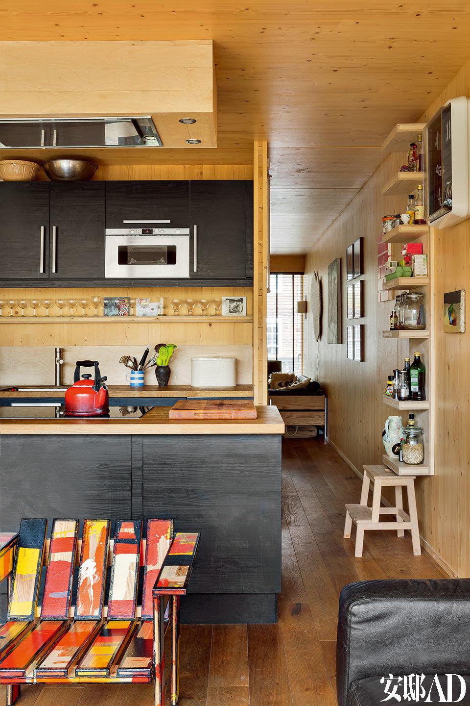 室内外都使用木板拼接而成,在视觉考量之外,这样做还能隔音, 并为整个家增添一种欢乐轻松的氛围,这种温暖的氛围可以通过视觉、触觉, 甚至气味切实感受到。从餐厅看向厨房,橱柜同样采用木制,是Richard Woods和Sebastian Wrong共同设计的,由 Established & Sons生产。
