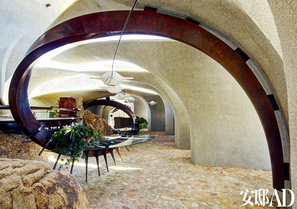 起居室的两根铜制横梁支撑起了玻璃台,起伏的屋顶区分开了各功能区。