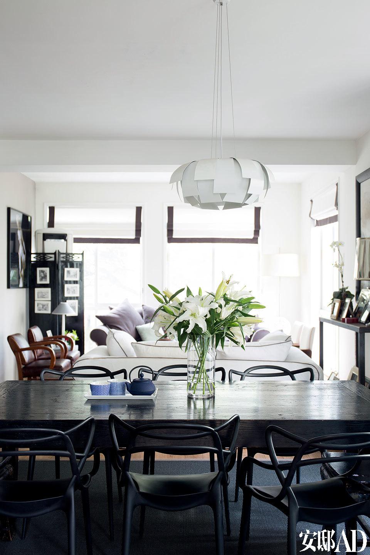 """一层起居室内的色彩以白色为主,无论是沙发还是靠垫都以细细的黑边""""勾勒"""",包括餐椅的选择也是黑色线条的""""构成""""。这些选择与搭配构成了室内风格的统一。"""