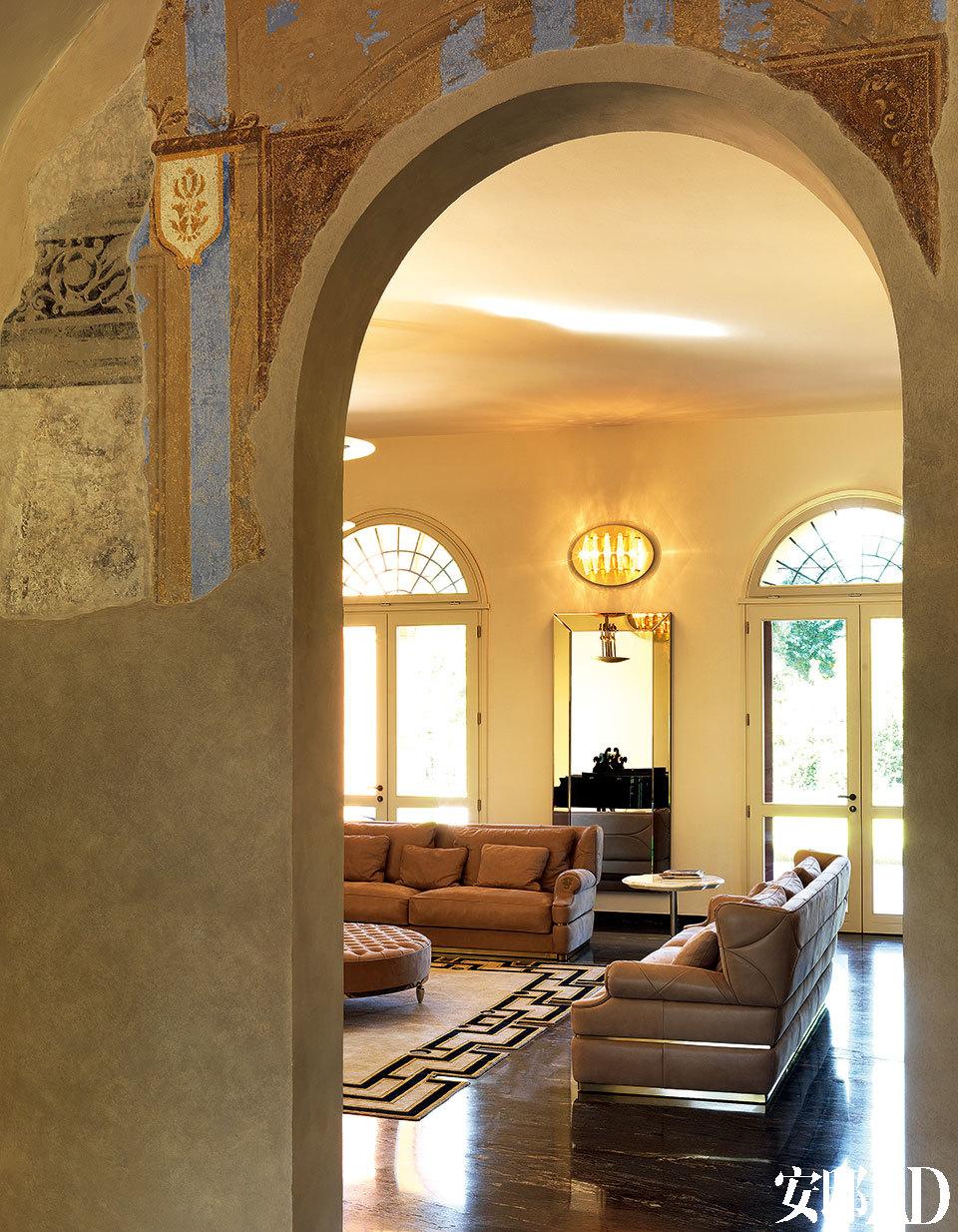 从走廊看向客厅,近处墙面上还部分保留着修复了的老壁画,客厅墙面上的椭圆形Benson壁灯由Samuele Mazza设计,壁灯下的装饰镜由Alessandro La Spada设计。