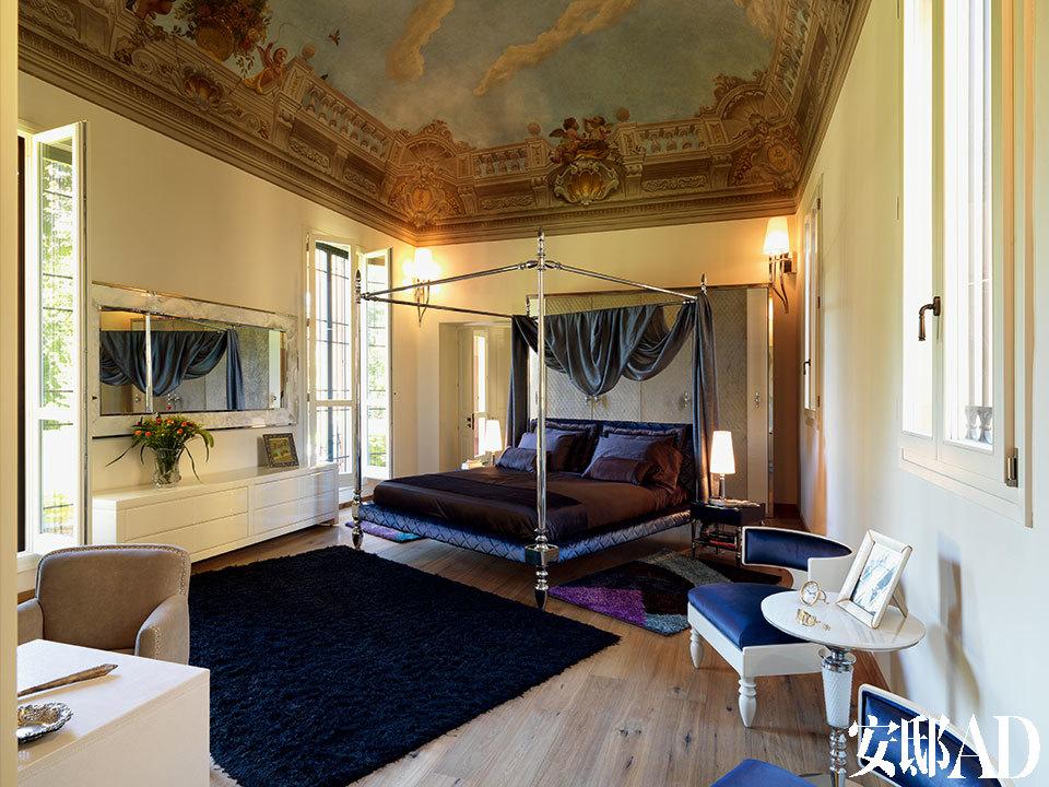 古老的彩绘天花还原了这座老宅昔日作为贵族狩猎别墅的面貌,更为每个夜晚装点出一场华美的梦。主卧室的天花板上原有的壁画装饰得以修复,Cador四帏柱床边的墙面上安着Brunilde壁灯,两侧摆着Ginevra床头柜,床头后面的Thorun衣柜由Alessandro La Spada和 SamueleMazza设计,两扇玻璃门之间摆着白色的Ludwig矮柜,上方的Kudrun化 妆镜也是Alessandro La Spada的设计,Maxim's茶几两侧摆着宝蓝色软包覆面的Bedwyr扶手椅,以上产品均来自Visionnaire。床两侧的Egg台灯由Philippe Montels设计,La Conca出品。