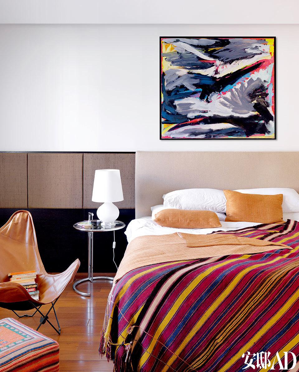 """""""很神奇,这个家就好像是专为我们的众多收藏品而设计的,我一看到它脑海中就有了主意,浮现出每个物件该摆放的位置。""""主卧室中,床头的墙面上挂着一幅由荷兰艺术家Jan Frenken创作的《Land scape》,丝质的抱枕及床旗来自柬埔寨的一家Amansara酒店用品店,彩条的藏毯从北京Torana购得。金属边几是Eileen Gray品牌,皮革质蝴蝶椅购自新加坡的Asiatique。"""