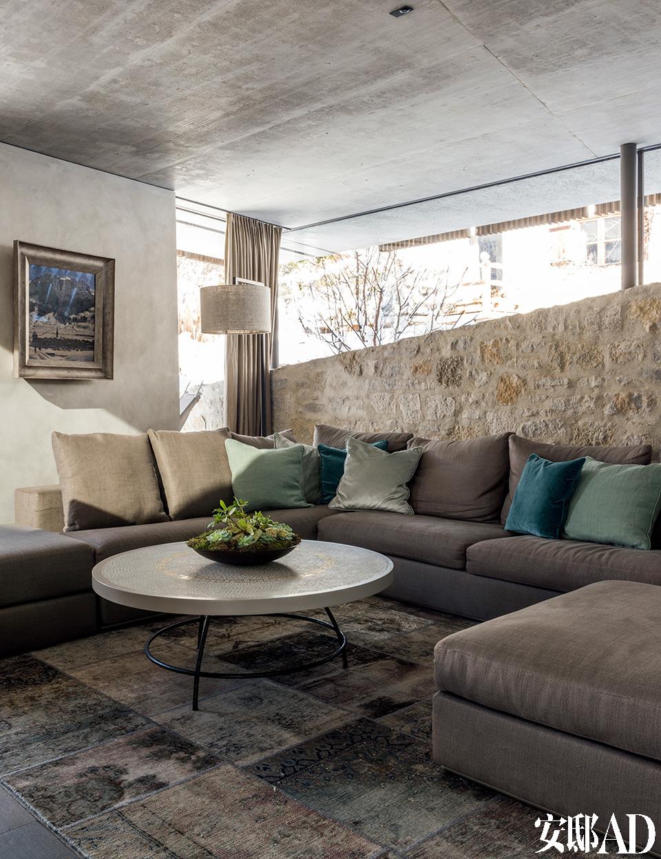 地面层的客厅里,舒适的沙发角落温馨宜人,墙面是由天然石材料制成的。
