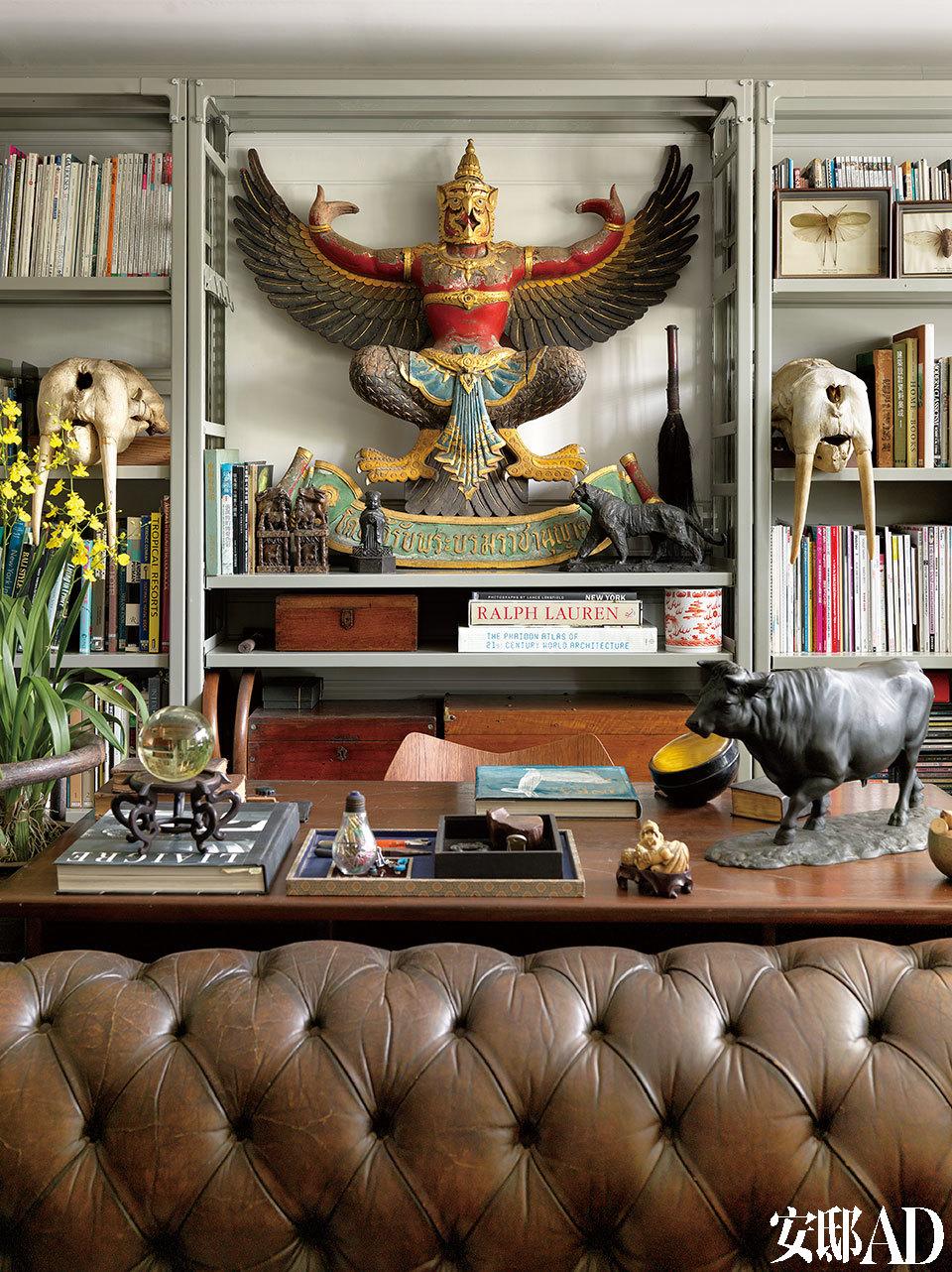 """客厅一角,其组合铁柜为一般办公空间所用,书架上的书籍是叶裕清从年轻时就一直爱看的书籍杂志。中间""""Garuda""""鸟头人身雕塑象征着泰国王室;两侧的海狮骷髅于英国买入;桌上的黑色""""牛""""为父亲送的礼物,为日本艺术家"""" 芳山""""作品。切斯特菲尔德风格沙发是比利时买的。"""