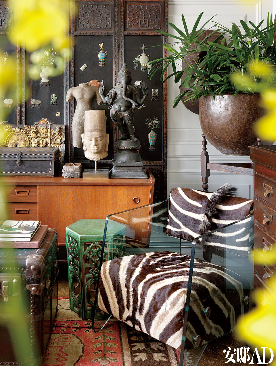 """叶裕清热爱非洲,各种动物标本以及骨架的收藏,成了他与非洲"""" 接触"""" 的秘径 。上世纪30年代的斑马皮椅,于一次纽约旅程中购得,后面的咖啡色老柜子为丹麦Retro风格的矮柜,皮椅后方的大花瓶为泰国椰子树干挖空制成的老花器;柜子上分别摆放""""Vishnu""""柬埔寨吴哥时期石雕、""""Ganesh""""泰国象头神铜像以及西藏皮革藏经盒等。"""