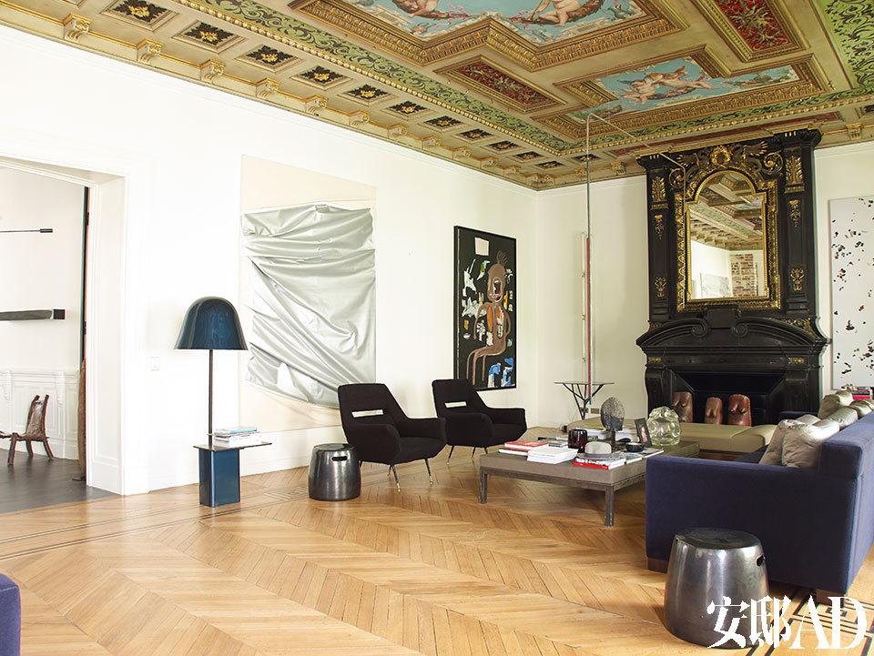 客厅的金色天花板上装饰着巴洛克风格的天使壁画,墙上黑底的丙烯油画是Jean-Michel Basquiat在1986年创作的《The Thinker》,两把1950年代的扶手椅购于一家古董店,客厅中央的茶几由Christian Liaigre设计,茶几上摆着Rit Sue Mishima创作的玻璃花瓶Cellula,茶几正上方悬垂的是Katinka Bock于2012年创作的Perfect Balance,材质为铜、钢、钢丝和纸。
