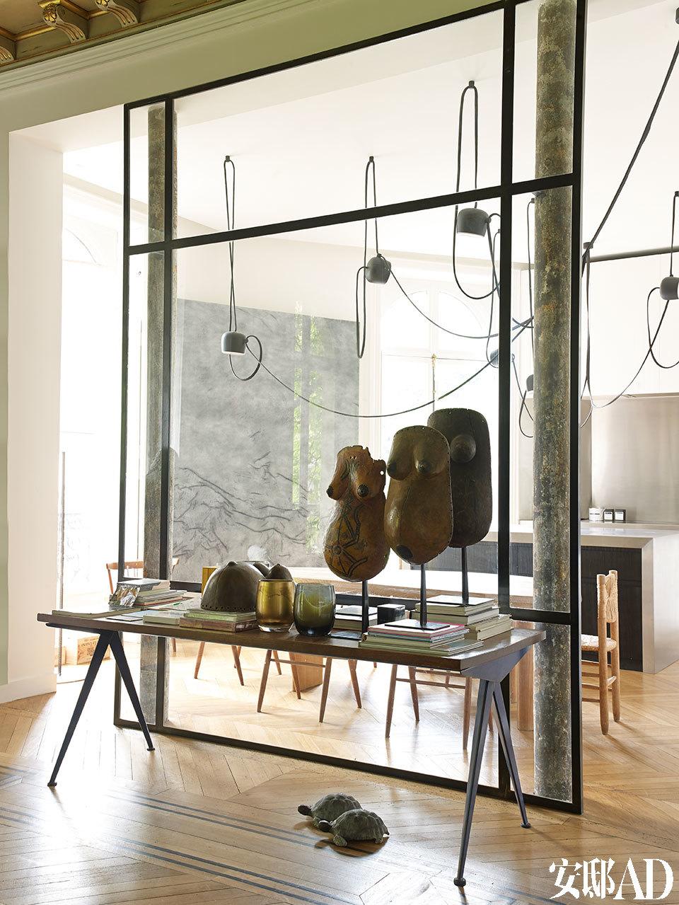 厨房和生活区的打通为家中带来更充沛的光线,也给这栋奥斯曼风格的老公寓融入一种当代loft氛围。一张由JeanProuvé设计的桌子Compas上,摆放着一些来自Zaire的部落艺术品。背景中,厨房墙面上的油画颜料、瓷漆画作由Rudolph Stingel创作于2010年。
