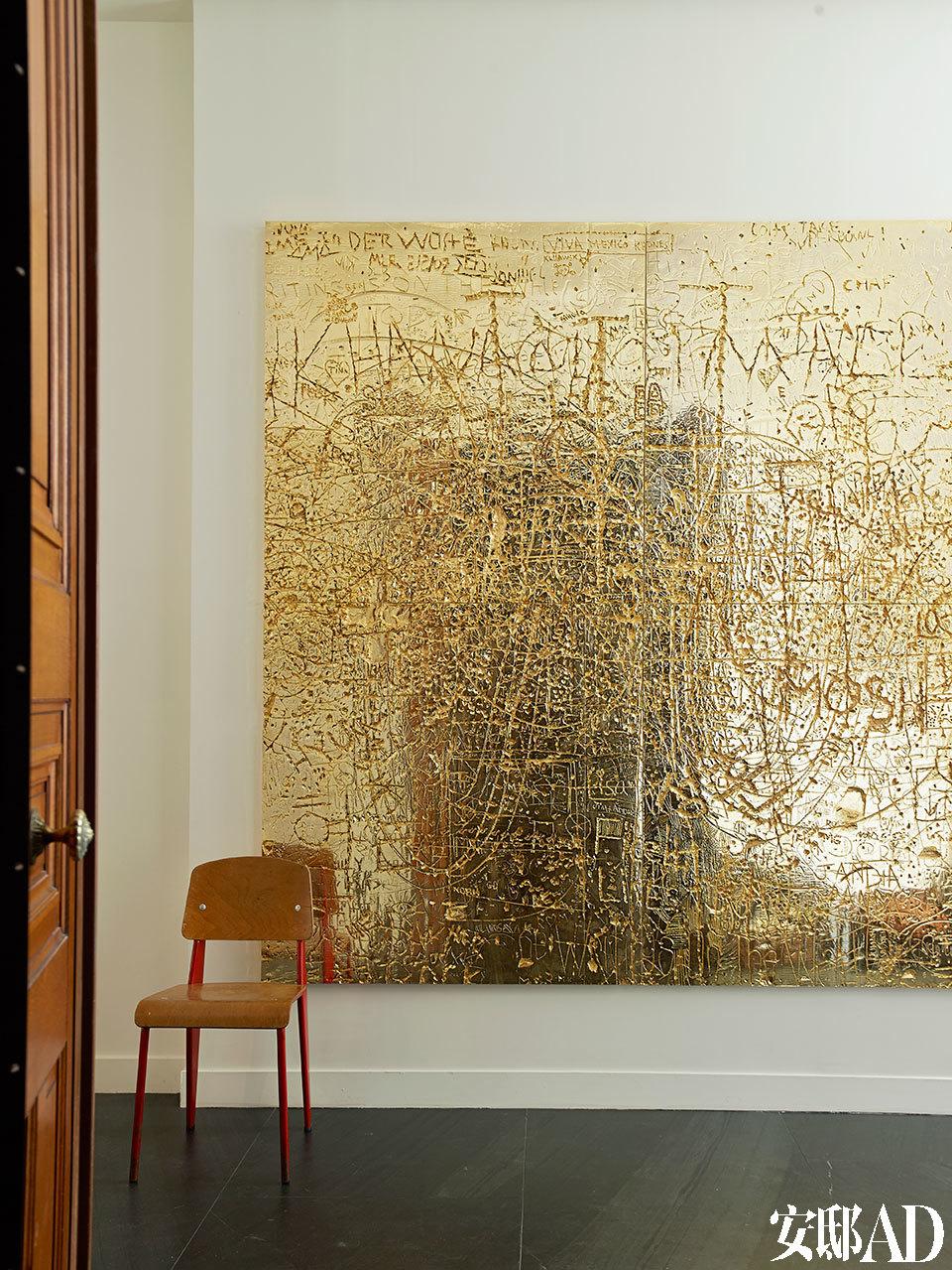 """主人将自己的家称作""""建筑中的贵族"""",画作就仿佛是这位贵族身上十分重要的装饰品。这幅Rudolph Stingel于2012年创作的艺术品为镀锌铸铜材质,在入口处欢迎着到访的宾客。它的左下角摆着一把Jean Prouvé设计的原版Standard椅。"""