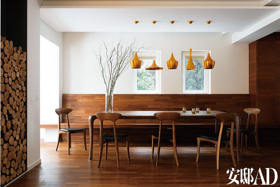 """客厅中,一片木色带来温暖、自然和雅致。来自兔宝宝品牌的樱桃木被铺装成地板、墙面饰板以及从墙上延伸出的一排长凳。设计师认为这种长凳可以让人与人亲密 地坐在一起,非常适合家人与朋友促膝谈话。""""大餐桌是我们家最聚人气的地方。吃饭之余,这里也是朋友们来家里闲聊的地方。我们常常沏一壶清茶、围桌而坐聊 古往今来的趣事……""""陈俊华说。近处的墙面上安装了一个钢质框架,里面码着的柴火段既可以当作壁炉的燃料,又是很美的装饰。餐桌上方的黄铜色吊灯是客厅的 亮点且非常带有艺术感,重点是每只只花了58元!"""