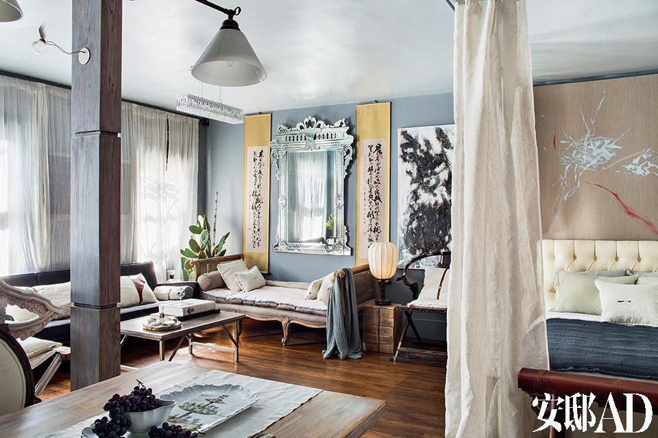 """客厅墙壁中央摆设的是沈伟10 多年前在意大利购买的威尼斯手工 制精雕挂镜,两旁是父亲的书法作 品,融合中西文化的典雅细致。客厅 的水晶灯也是沈伟的最爱之一,""""水 晶充满正面力量,又有种神秘感,充 满很多想象。""""长椅和茶几选购于 ABC 连锁品牌家具店。桌灯则是于北 京传统家具店寻宝所得。喜欢宽敞空间感的沈伟,将客厅与卧室间的隔断都打掉了,以素色亚麻布帘作为区隔,气质不凡。"""