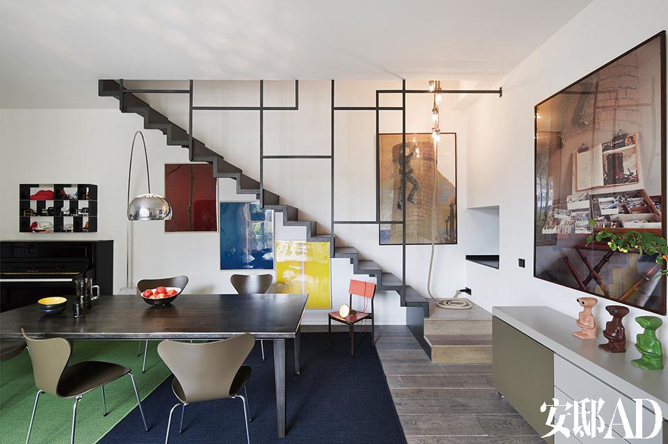 餐厅全景,悬空的黑色不锈钢楼梯是绝对的亮点,也是安装施工时最有挑战性的地方。全部楼梯台阶主要以墙面作为承重点,因此而形成一种干净利落的悬浮感。楼梯的黑色矩形格子边框,以及下方的红黄蓝三色画作,成为了对蒙德里安经典风格的活学活用。