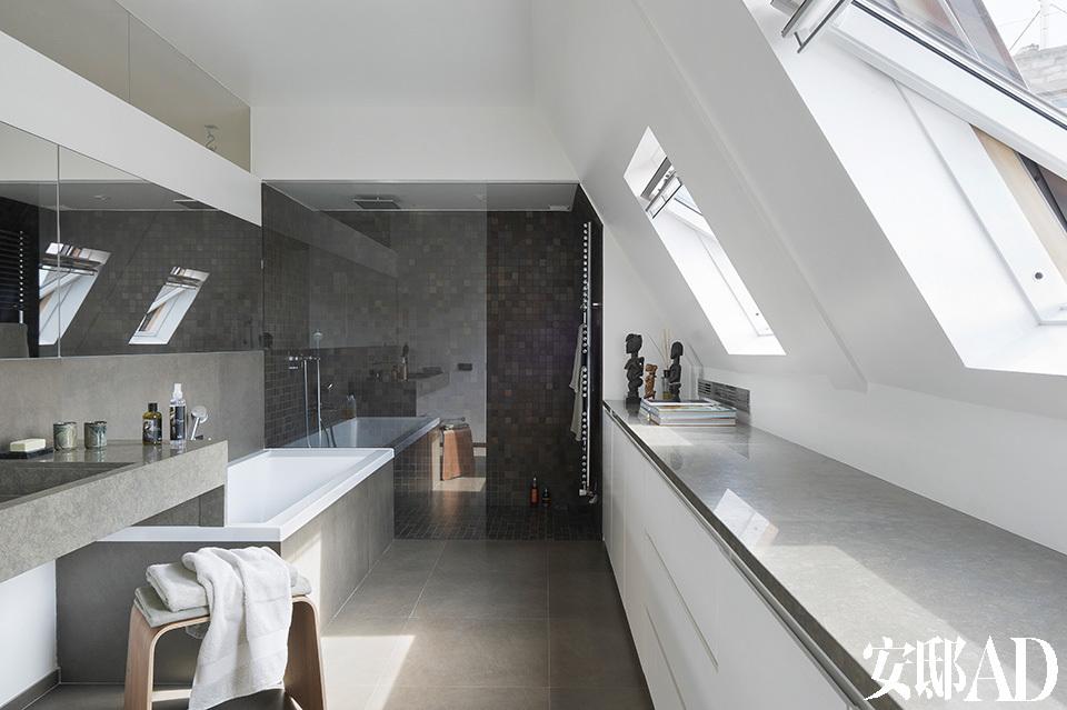 位于阁楼的一间主浴室从地面、浴缸到储物柜台面均铺着 Cascais地砖,浴缸来自Raboni,窗前的雕塑摆件来自非洲。