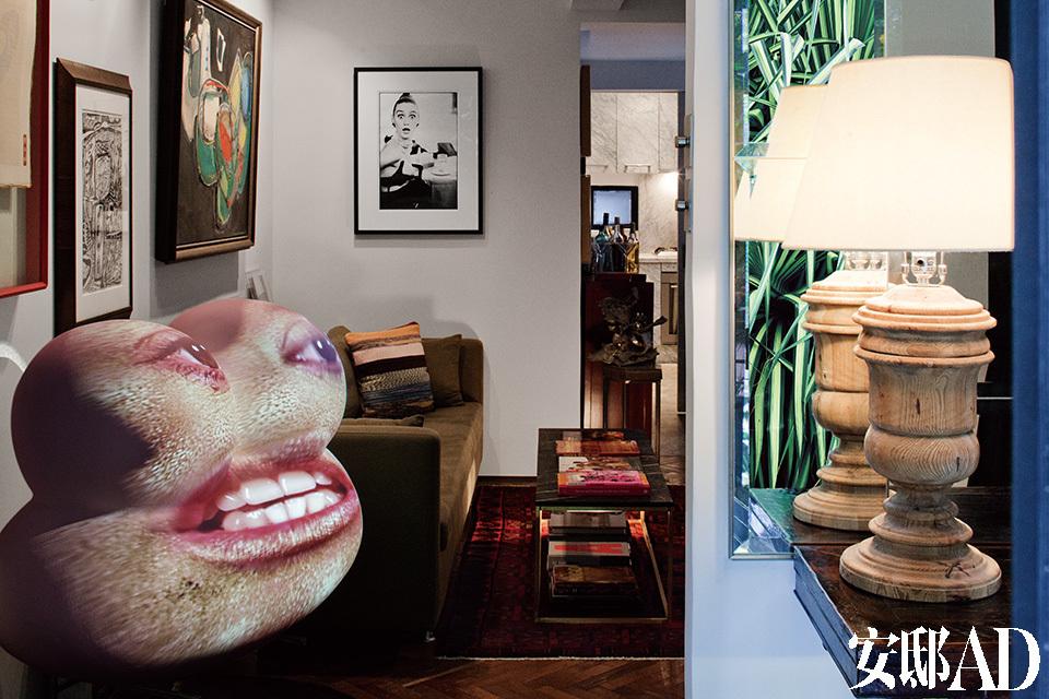 """侧看客厅,右边是入口处,桌案后的镜子正好反射出户外的浓郁绿叶,材质温暖的回收松木台灯由屋主Del Vecchio设计。最抢眼的物件莫过于一进门就能看见的客厅中的""""怪脸"""",它是美国视觉艺术家Tony Oursler的投影雕塑作品,一个古怪的问好。客厅中优雅的黄铜细框大理石茶几和配套的皮革坐凳带来了现代美感。"""