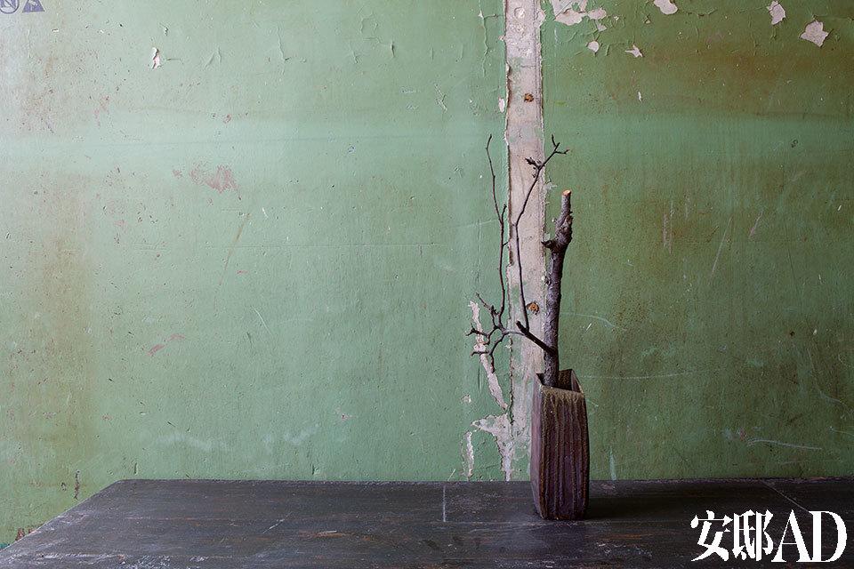 """在建造无用生活空间时,所有的隔墙都经过重新打造,唯有这面墙被保留下来,承载这座建筑过往作为胶印厂的历史,墙面的一角甚至还留有一张当时厂里的""""通知""""。图中的老木柜和陶土花瓶都是马可的收藏品。"""