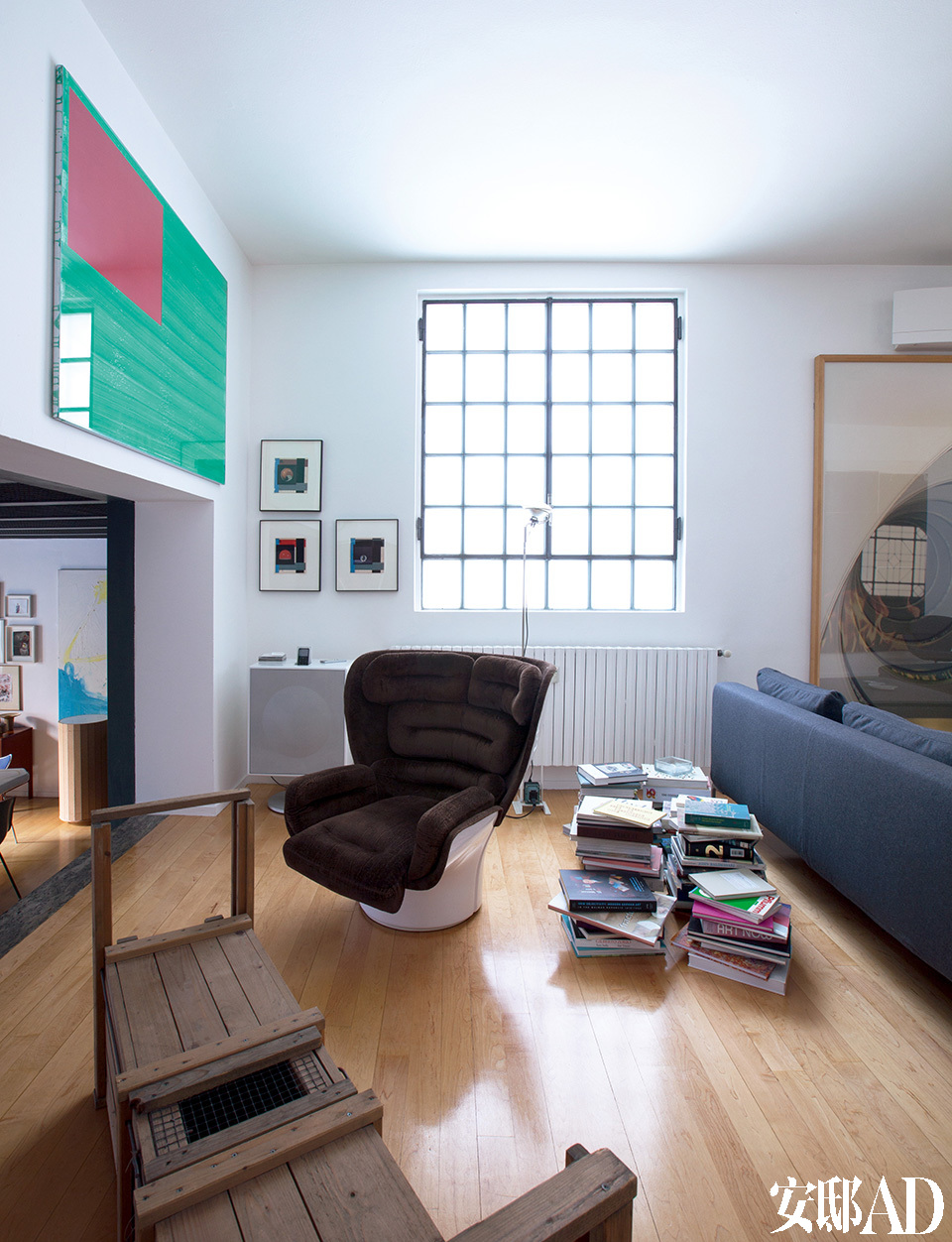 左墙上的铝框水粉画来自艺术家Wade Guyton,地上的木头雕塑来自Andreas Slominski,Ray 模型沙发椅出自Antonio Citterio B&B Italia,扶手椅是大师Joe Colombo 于1965年设计的。
