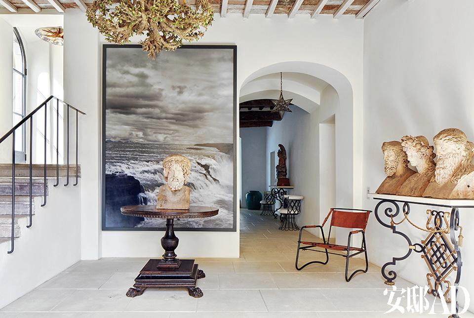 活动区左侧的台阶一直通向卧室。摄影作品来自德国艺术家Nina Pohl。房屋中间的圆桌为古董收藏。右侧的操作台和后侧的白色座椅来自法国工匠大师Gilbert Poillerat。右侧的铁制皮革座椅为 法国现代主义家具经典代表作品, 由Jacques Adnet设计。