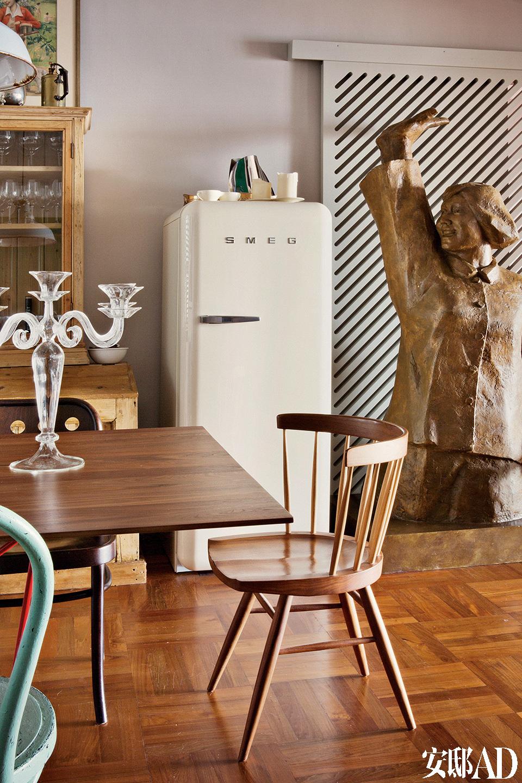 餐桌旁的椅子是George Nakashima为Knoll设计的经典木椅,Smeg的1950年代复古冰箱旁,配了一尊王广义的《唯物主义者》雕塑。