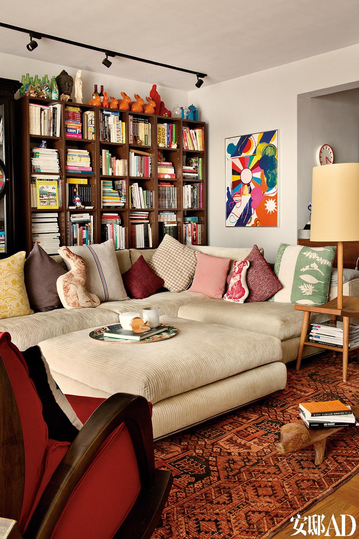 """""""我拜访过一些那种特别高雅精致的房子,进去以后完全无法放松,所以舒适感是我们对家的第一要求。""""沙发里堆满了舒服的抱枕,后面整面墙的书架放满了书,墙上挂着一幅日本艺术家Tsuruko Yamazaki的作品《无题》,地上铺着古董地毯,购自一位香港经销商。"""