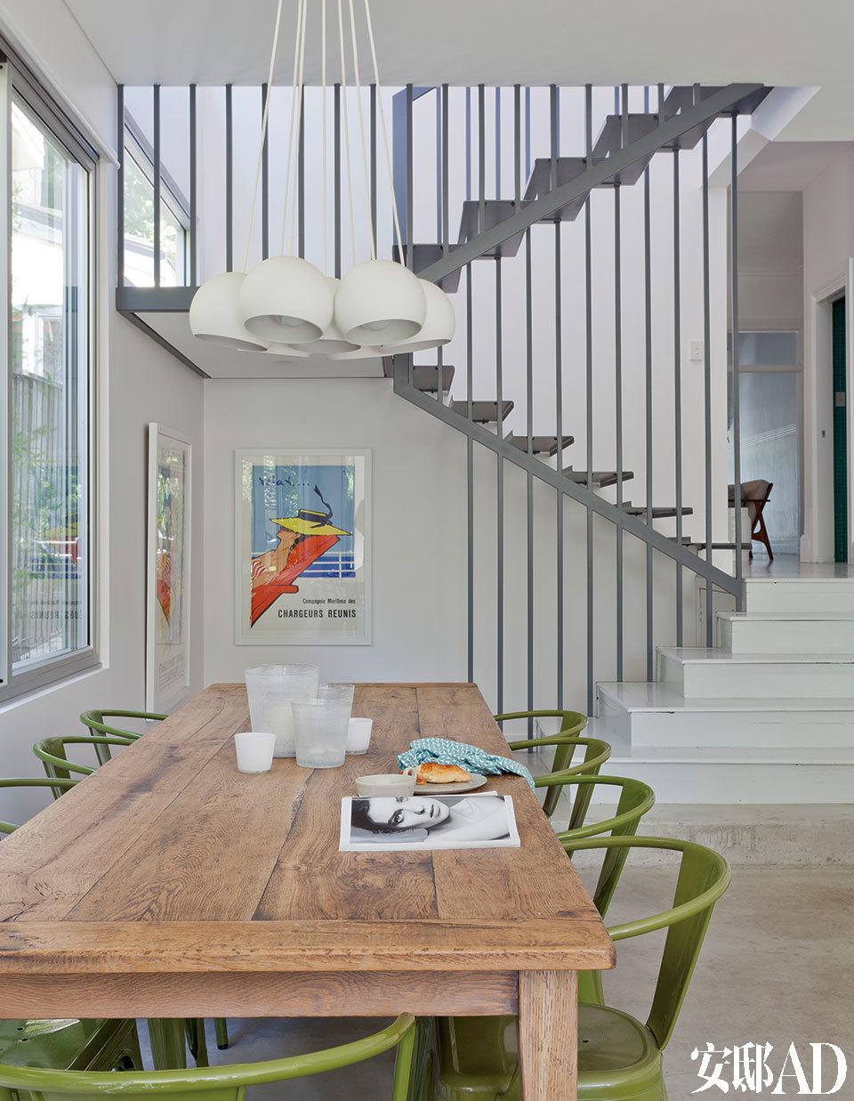 """绿色餐椅与窗外景致呼应,木质餐桌与钢结构楼梯则冲撞出原始与现代的双重气息。餐桌旁挂着两幅欧洲的海报,主人购买于夏威夷。其中正对餐桌的那一幅名为""""Relax"""",是René Gruau 1961年的作品。餐椅是Matt Blatt绿色复刻版Tolix餐椅。吊灯是来自Hub Furniture的白色Toss-B 7球吊灯,桌上的花瓶则来自The Country Trader。"""